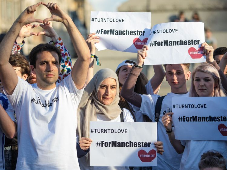 People hold up signs in Trafalgar Square, London, during a vigil for the victims of the Manchester Arena terror attack