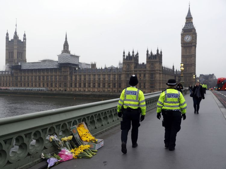 Police officers walk past floral tributes placed on Westminster Bridge