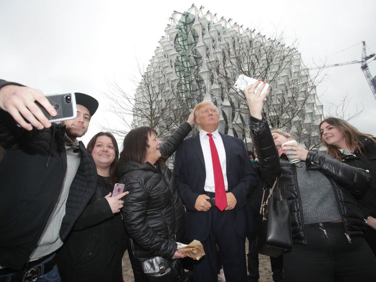 People take selfies with the Madame Tussauds wax figure of US President Donald Trump outside the new US Embassy in Nine Elms, London