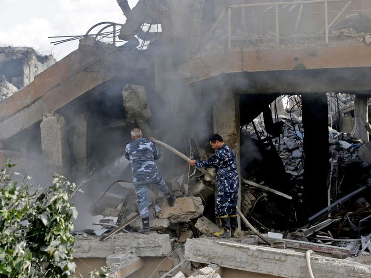 Syrian soldiers extinguish a fire in the wreckage of the part of the Scientific Studies and Research Centre in Damascus