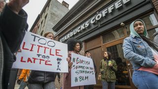 Protesters gather outside of a Starbucks in Philadelphia where two black men were arrested