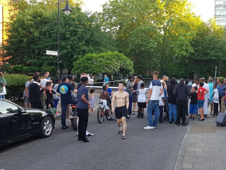 A large crowd gathered outside the cordon in Peckham