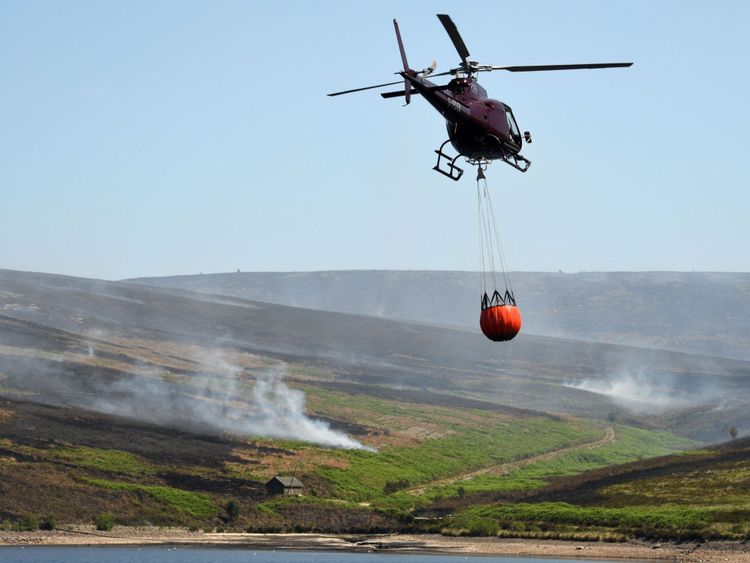 A helicopter carries a container with water from Upper Swineshaw Reservoir before dumping the water onto smouldering fires on Saddleworth moor
