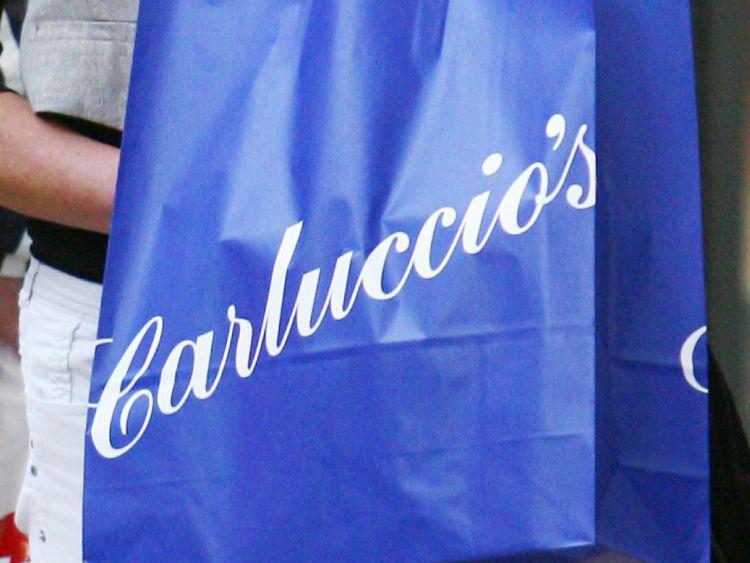 A shopper carries a Carluccio's bag