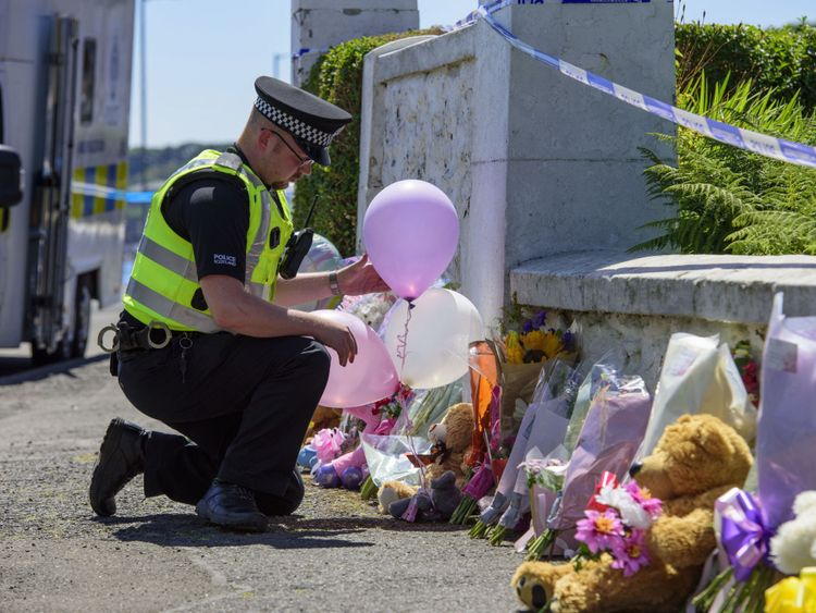 A police officer leaves balloons near a house on Ardbeg Road
