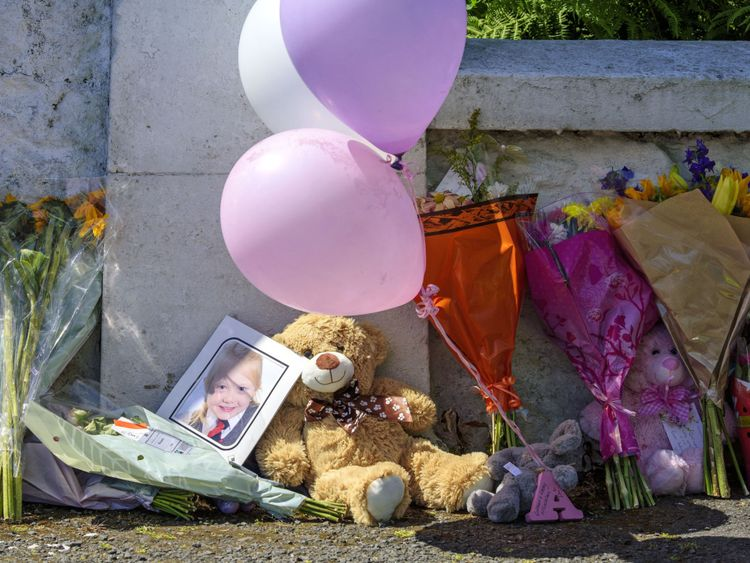 Balloons and a teddy bear are left against a wall