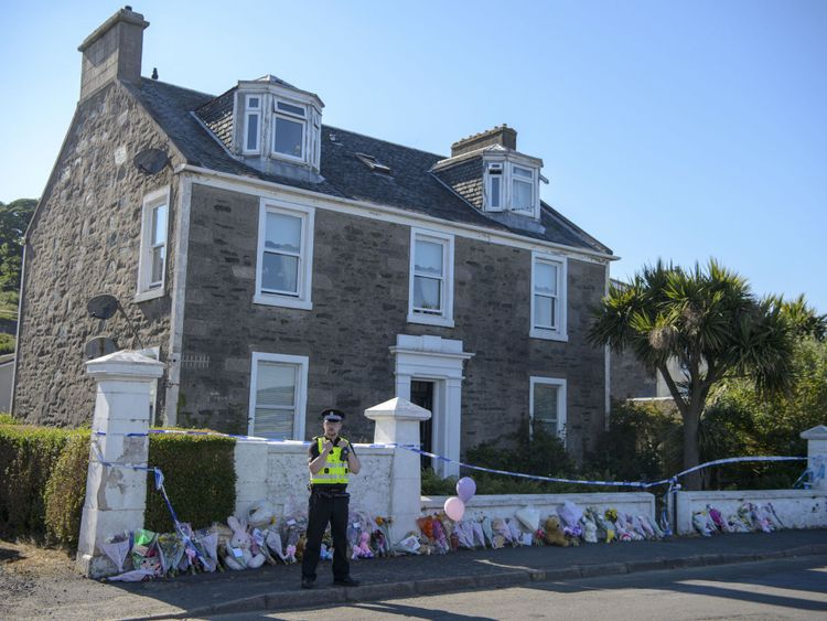 Police stand outside the house that Alesha MacPhail went missing from