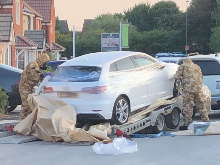 A car is wrapped in plastic film by personnel in military fatigues. Pic: James Street