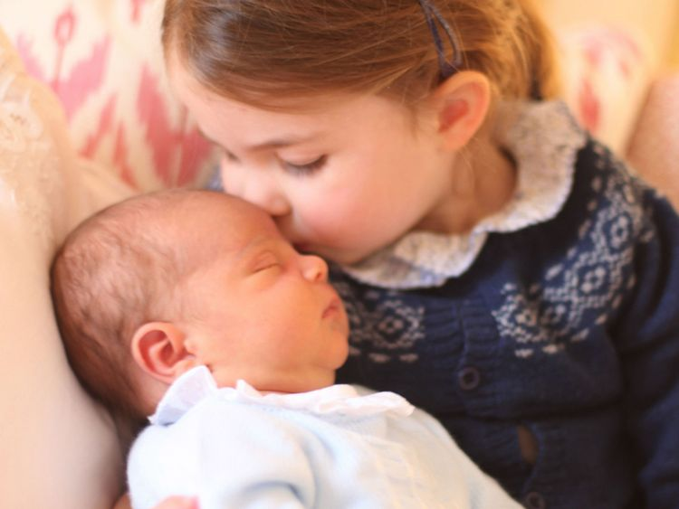 Princess Charlotte holding Prince Louis on her birthday