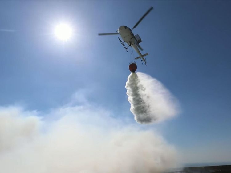 A helicopter drops water on the fire from the air