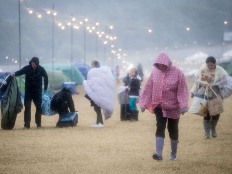 Festival goers walk in the wind and rain at Camp Bestival on 29 July