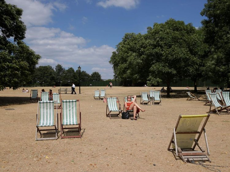 Visitors to Hyde Park sit on deck chairs on the dry brown grass in London on July 23