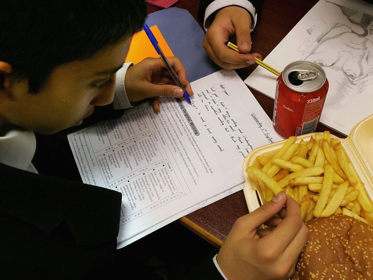 LONDON - OCTOBER 5: In this photo illustration a school student eats a hamburger and chips as part of his lunch which was brought from a fast food shop near his school, on October 5, 2005 in London, England