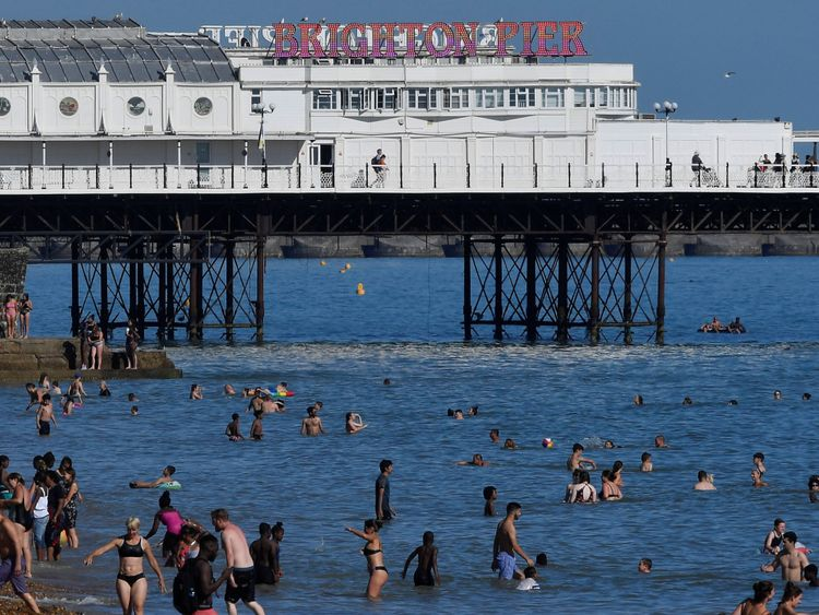 Beachgoers cool down in the sea during hot weather at Brighton in southern Britain, August 3, 2018. REUTERS/Toby Melville