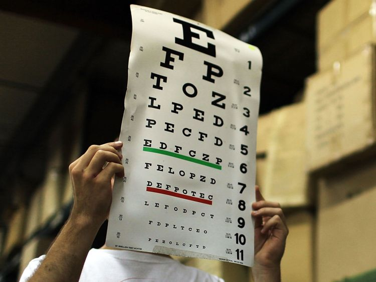 CHESHIRE, CT - JUNE 24: Jason Quint, a medical student, holds up an eye exam for a patient in a garage at a flower nursery serving as a healthcare clinic for migrant farm workers on June 24, 2010 in Cheshire, Connecticut. The University of Connecticut Migrant Farm Worker Clinics visits area farms and nurseries from June to October offering health screenings and preventive health education for migrant farm workers and their families. Partnered with the Connecticut Area Health Education Centers (C
