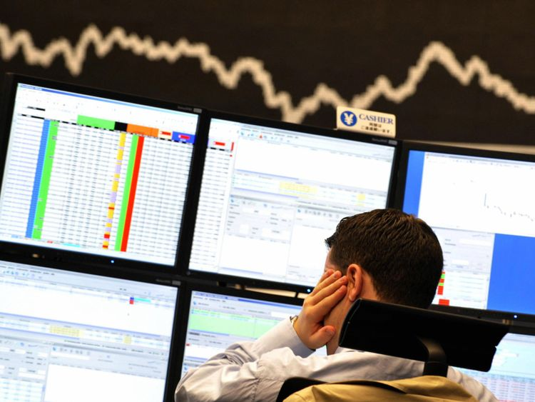 A broker looks at his screens