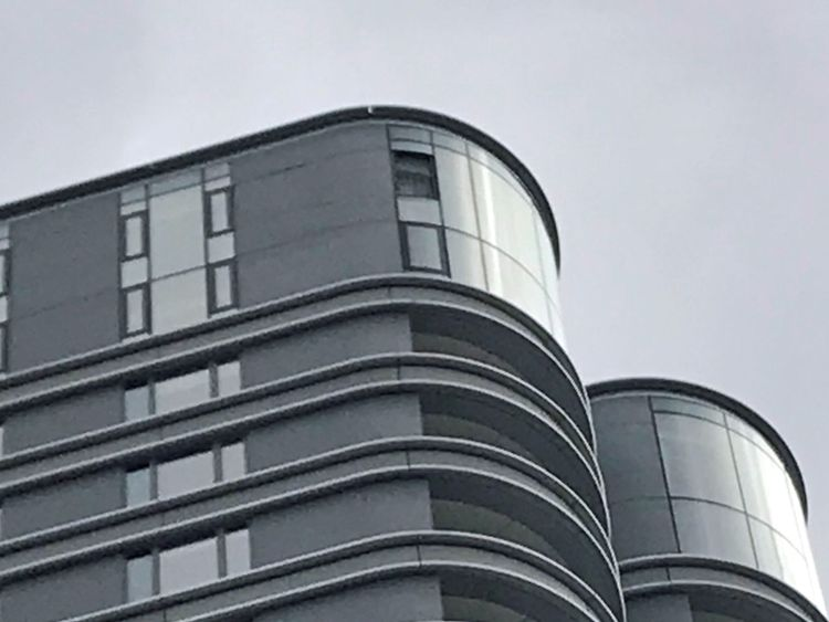 A photo of The Corniche apartment building appears to show a missing window